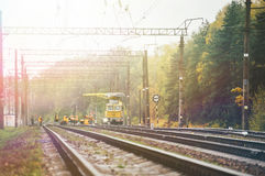 Workers in orange raincoats repair railroad. On sunny day Stock Images