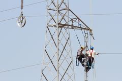 Workers over a high tension tower making reparations. Pair of electricians repairing cables over a high tension tower in Spain Royalty Free Stock Photos