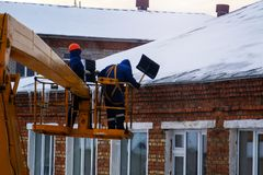 Workers in overalls and orange helmets on the crane basket remove icicles from roof of the house on a winter day - cleaning the stock photo