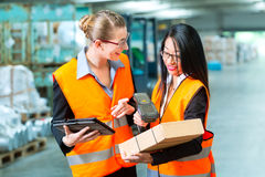 Workers with package in warehouse of forwarding. Logistics - female worker or shipper and employee or colleagues, with protective vest and scanner, scans bar stock image