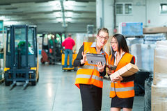 Workers with package in warehouse of forwarding. Logistics - female worker or shipper and employee or colleagues, with protective vest and scanner, scans bar stock photography