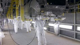 Workers are painting car bodies by airbrushes, they are wearing protective overalls stock footage