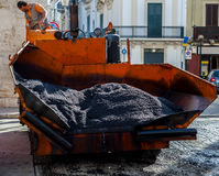 Workers on a paver machine. Control the drafting of a new layer of asphalt for maintenance of city streets Stock Photography