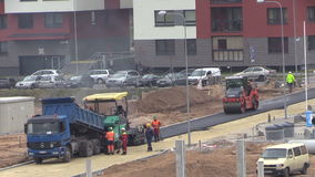 Workers pavers work with asphalt spreader and roller machines. Apply first asphalt layer in living district. Static shot on Canon XA25. Full HD 1080p stock video footage