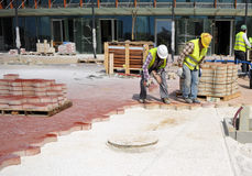 Workers in paving the sidewalk with concrete pavers Royalty Free Stock Image
