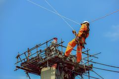 Workers people and safety man sprinkle from up high. Workers people and safety man sprinkle from up high with safety harness, safety equipment and safety belts royalty free stock images