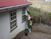 Workers performing maintenance on a house in the tropics. A man and woman preparing window ledges for varnishing in the caribbean stock footage