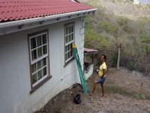 Workers performing maintenance on a house in the tropics. A man and woman preparing window ledges for varnishing in the caribbean stock video footage