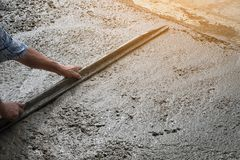 Workers person not wearing dirt boots digging with hoe shovel. On concrete floor, Construction workers leveling concrete pavement. Upgrade to residential street Royalty Free Stock Photo
