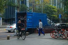 Shenzhen, China: workers carry bicycles in the street. Workers place bicycles in the street, this is mobike royalty free stock images