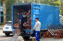 Shenzhen, China: workers carry bicycles in the street. Workers place bicycles in the street, this is mobike royalty free stock photos