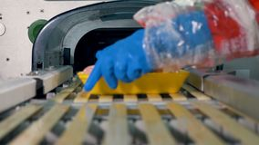 Workers place trays with sausages on a wrapping line. stock video
