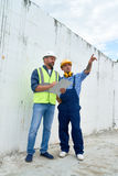 Workers Planning Construction. Portrait of construction foreman discussing building plans with supervisor,   both wearing hardhats on site Royalty Free Stock Photo