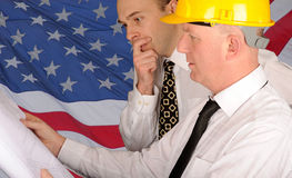 Workers With Plans. Workers in shirts and hard hats holding plans in the front of an American flag Royalty Free Stock Images