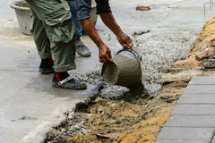 Workers pouring concrete. Construction workers pouring concrete building road Royalty Free Stock Images