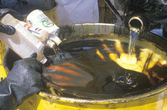 Workers pouring toxic wastes into a metal drum Stock Photo