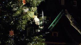 Workers preparing the Christmas tree in central square. Strasbourg, France - circa 2018: Workers on top of telescopic crane in central Place Kleber preparing stock video footage