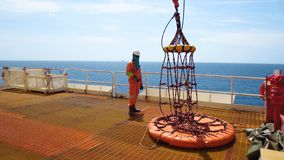 Workers are preparing the personal basket to lift by the crane to the offshore platform,. Transfer crews by personal basket from the platform to crews boat royalty free stock photos