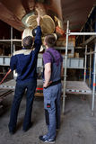 Workers at the propeller of passenger vessel Stock Photos