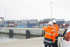 Workers in protective clothing examining cargo in shipping yard royalty free stock image