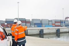Workers in protective clothing examining cargo in shipping yard royalty free stock photo