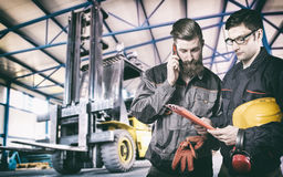 Workers in protective uniform in front of forklift Stock Photography