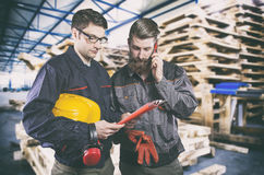 Workers in protective uniform in front of wooden pallets Royalty Free Stock Image