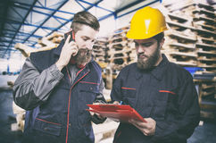 Workers in protective uniform in front of wooden pallets Royalty Free Stock Photography