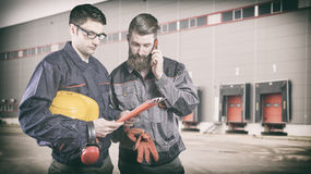 Workers with protective uniforms in front of shipping warehouse Royalty Free Stock Photos