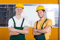 Workers in protective workwear standing with arms crossed Stock Photos
