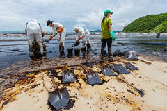 The workers from PTT use the shovel to remove the crude oil Stock Image