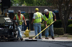 Workers raking asphalt Stock Image