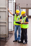 Workers recording containers. Shipping company workers recording containers at the warehouse Stock Photography