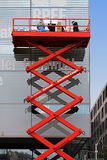 Workers on red telescopic platform attach advertising Royalty Free Stock Images