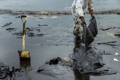 Workers remove and clean up crude oil spilled with absorbent pap. Er from Prao Bay on July 31, 2013 in Samet Island, Rayong, Thailand Stock Photos