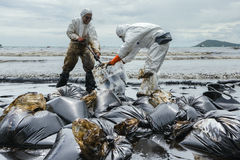 Workers remove and clean up crude oil spilled from Prao Bay Royalty Free Stock Images