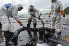 Workers remove and clean up crude oil spilled from Prao Bay Royalty Free Stock Photography
