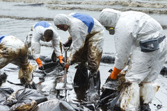 Workers remove and clean up crude oil spilled from Prao Bay Stock Image