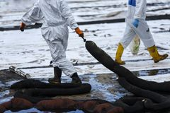 Workers remove crude oil from a beach Stock Image