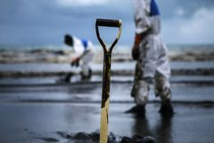 Workers remove crude oil from a beach Royalty Free Stock Photography