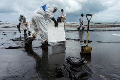 Workers remove crude oil from a beach Stock Photo