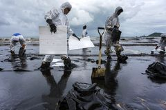 Workers remove crude oil from a beach Royalty Free Stock Photos