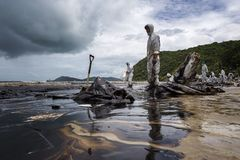 Workers remove crude oil from a beach Royalty Free Stock Images
