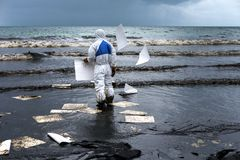 Workers remove crude oil from a beach Stock Photos