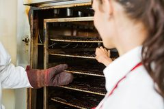 Workers Removing Dried Meat Slices From Oven At Stock Images
