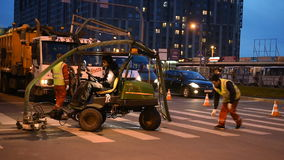 Workers renovating the road marking. St. Petersburg, Russia - May 4, 2015: Workers make renovation of the road marking on a crossroad in evening. Renovation and stock video footage