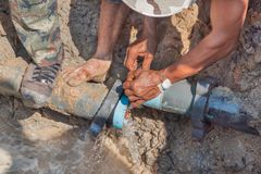 Workers repair leg stomp on Plumbing broken to hole fix water leak at big on the road.  Royalty Free Stock Photos