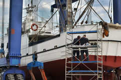Workers repairing a fishing boat Stock Images