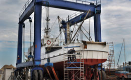Workers repairing a fishing boat Royalty Free Stock Photo
