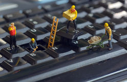 Workers repairing keyboard. Macro Workers figurines repairing keyboard Royalty Free Stock Photography